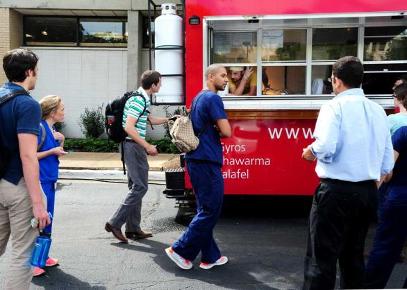 EMILY ROSE BENNETT/STAFF Students wait for orders at the Laziza Mediterranean Grill foodtruck outside the student center at the Health Science campus. The owners have secured a six-month contract on the campus.