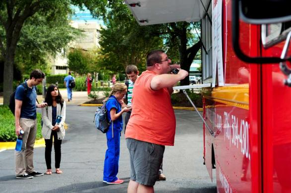 EMILY ROSE BENNETT/STAFF Students wait for their orders at Laziza Mediterranean Grill food truck outside the student center at Georgia Regents University's Health Science campus as it undergoes installation of new dining options