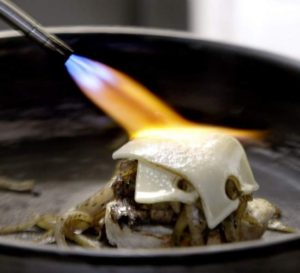 Chef Daniel uses a flame to finish the Swiss cheese on top of a steak slider.