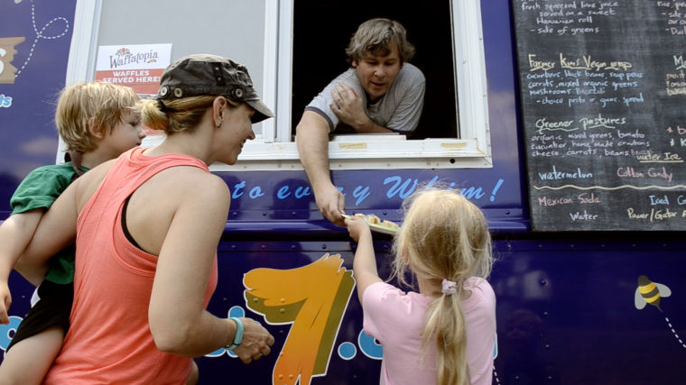 Mike Gerenda (center), owner of Foodtruck7, hands out a food order during a recent stop at Falls Township Park.