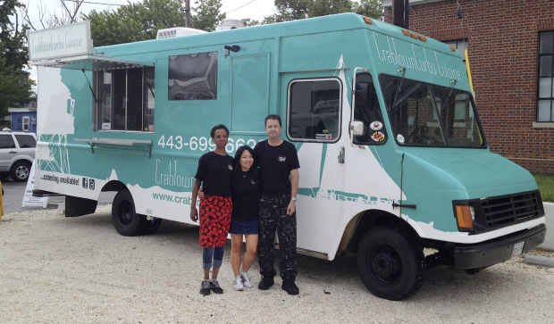 From left: Dana Robinson, FNU Hanny and John Talman pose next to Talman's CrabTown Curbs truck near the Annapolis Maritime Museum during a recent fundraiser.