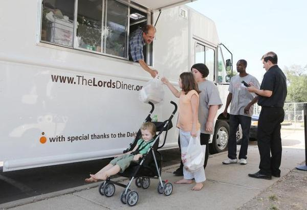 Lilly Cluck gets food from the Lord's Diner food truck for herself and her sisters (in front and behind her) at Friendship Park. This truck served 16,177 meals in July at this location. (August 4, 2014) Jaime Green/The Wichita Eagle