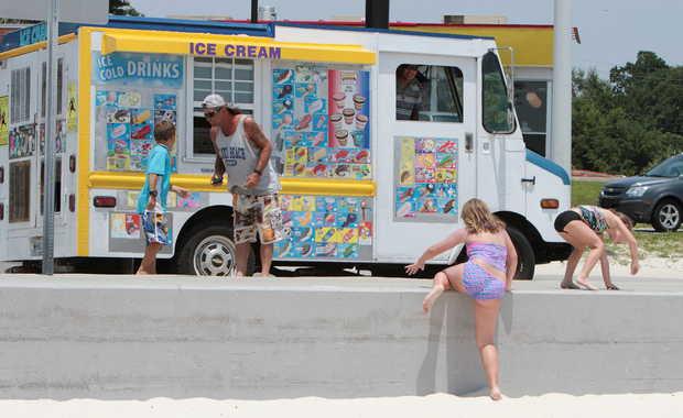 OHN FITZHUGH/SUN HERALDCustomers gather to buy ice cream from Minh Nguyen's ice cream truck on the Beach in Biloxi on Thursday, July 31, 2014. JOHN FTIZHUGH — SUN HERALD