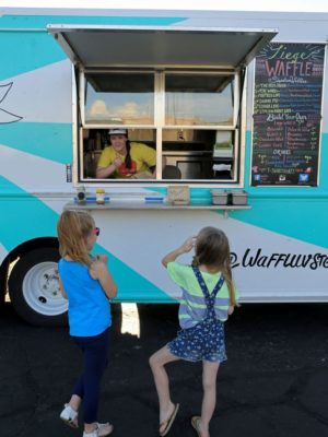 Chloe Miles, 7, and her sister Claire, 6, wait for waffles from  Waffle Love on Monday during the Food Truck Roundup at Hurst General Store in St. George.  (Photo: Brian Passey / The Spectrum & Daily News)