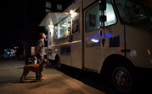 MARK DAVIS/THE WORLD-HERALD  Rob Henry, with his dog Braddick, orders from the Localmotive Food Truck parked in the Old Market.