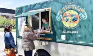Kathleen Montana, left, awaits her Lola sandwich as Liz Ward is handed her Ange sandwich by owner Erica Dionne at the Muthah Truckah Food Truck. Gordon Chibroski/Staff Photographer