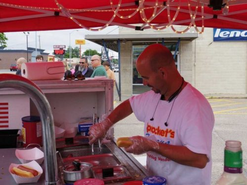 Pat McClure of Sprocket's Famous Freedom Dogs serves a customer on Thursday at the Kearney Food Truck Rally. In addition to Sprockets, four other food trucks were present — Grinders, The Flippin' Sweet, The Food Truck, and Natalie's Mexi-Cart.