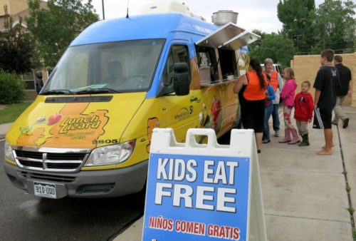 Children line up at the new Lunch Lizard food truck in Grand Junction.  It brings federally-funded free lunches to children who might otherwise go without.  (Megan Arellano/CPR News)