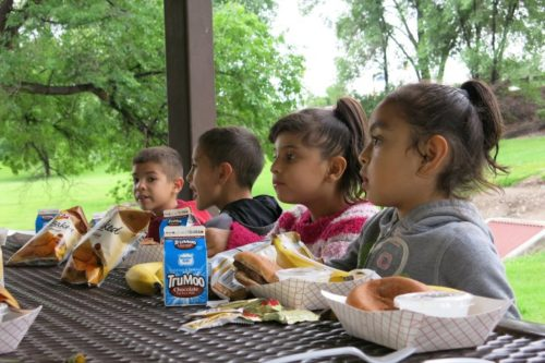 A group of kids enjoy a makeshift picnic in Grand Junction, courtesy of the Lunch Lizard.  It brings federally-funded lunches to children who might otherwise go without. (Megan Arellano/CPR News)