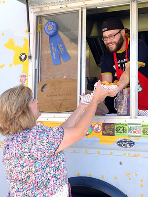 Josh Gardner, owner and chef of The Epic Cure food truck, hands a food order to a Waco Elementary School teacher Wednesday. The truck drives to the school twice a month to serve to teachers who have few lunch options nearby.