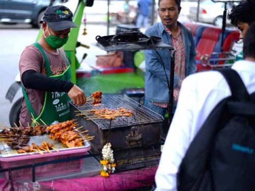 A street-side vendor doles out chicken satay