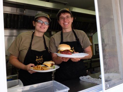 Melissa Krahn and Carey Friesen serve up sausage sandwiches from Pioneer Meats at the Hast Wurst food truck.