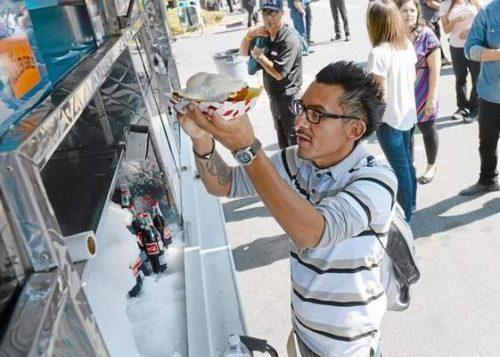 Richardo Mendoza of San Bernardino takes his order from Piaggio Gaucho on Wheels during the Third Thursdays Food Fest in downtown San Bernardino in 2014. Staff File Photo