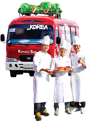 """Ryu Si-hyeong, center, CEO of """"Kimchi Bus""""  poses with kimchi in front of his food truck with  his two chefs and co-workers Jo Seok-beom,  left, and Kim Seung-min. / Courtesy of Kimchi Bus"""