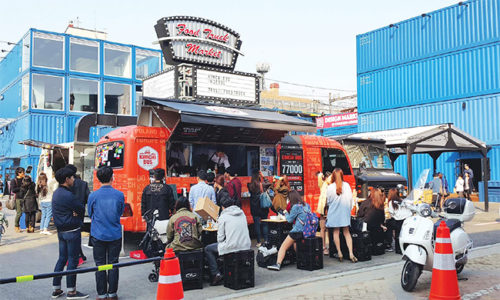 """Customers line up in front of a """"Kimchi Bus"""" food truck  parked inside Common Ground, a shopping complex near Konkuk  University in Seoul. / Courtesy of Kimchi Bus"""