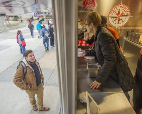Lauren Keskett, worker at the Tasty Traveler food truck, talks to Chris Lericos, senior in graphic design, as she hands him his food on Jan. 19, 2016. Tasty Traveler is one of several different food trucks that will be coming to campus this semester while the K-State Union remains under construction. (George Walker | The Collegian)