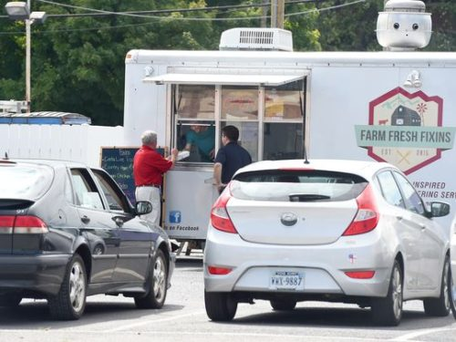 Costumers gather at the window of the Farm Fresh Fixin's food truck — one of three food trucks operating in a lot behind Kline's Dairy Bar in Waynesboro on Wednesday, Sept. 9, 2015.(Photo: Mike Tripp/The News Leader)