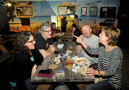 Suzanne Wertman (from left,) Mike Chevoor, Billy Quetel and Kathy Quetel enjoy a meal from the 2 Bros Coastal Cuisine food truck at Flytrap Brewing Saturday  Dec. 26, 2015.