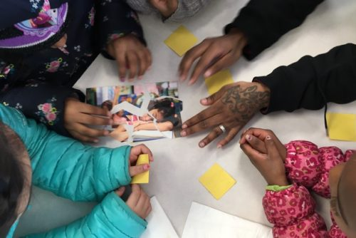 With the help of an Eastman Egg staffer,  students piece together a puzzle showing a tired- looking girl who, they agree, probably didn't eat a good breakfast.  [DNAinfo/Janet Rausa Fuller]
