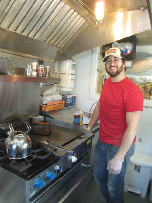 """Matthew Glatz stands ready to cook inside his """"tiny house"""" food truck, The SaltBox Cafe,  on Sunday River Road in Newry. He offers a genuine daily perk: The first customer gets a free coffee."""