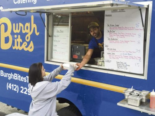 "David Mayernik Jr. | Tribune-Review Samantha Lorentz, 19, of Moon, purchases food  from Ricci Minella's Burgh Bites truck at the first  ""Food Truck Friday"" of the summer in Heidelberg  on May 20."