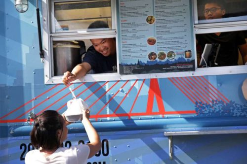 Take a look at some of Seattle's best-named food trucks. Above, Ferry Ijaya hands an order out the window of the Thai-U-Up food truck to Kylie Knowles on Tuesday. Knowles is a frequent patron of the truck; her go-to dish is the Veggie Delight.
