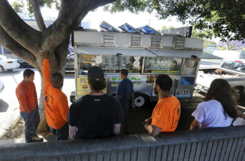 Customers wait for their orders to be made outside the Tacos Ariza food truck  on April 28, 2016, in Los Angeles. LOS ANGELES TIMES