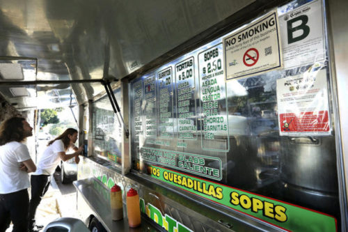 Customers prepare to make their orders at  the Tacos Ariza food truck April 28, 2016, in Los Angeles.  Food trucks have scored poorly on health inspections.  LOS ANGELES TIMES