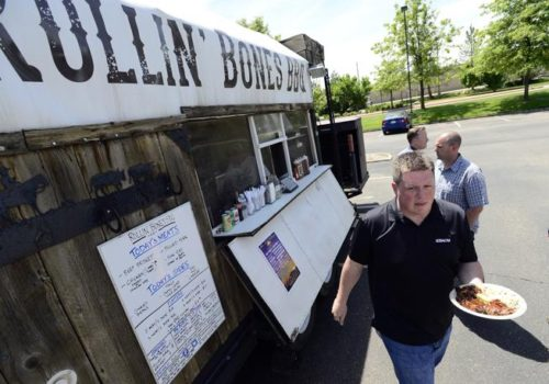 David Porter collects his meal from a food truck,  Rollin' Bones BBQ, which was serving food on  Central Avenur in Boulder on Friday.  (Cliff Grassmick / Staff Photographer)
