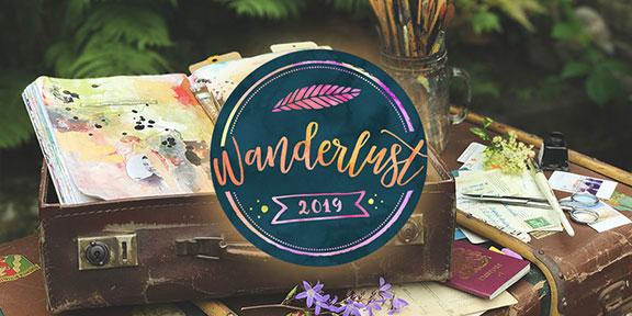 Wanderlust logo with colourful journal and paintbrushes on top of a suitcase