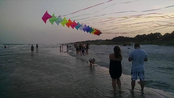 Kites flying on the beach at sunset