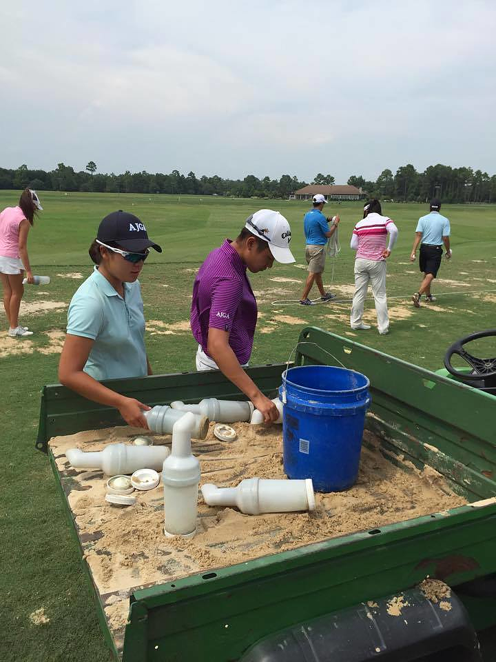 Two IJGA students help fill divots during an AJGA event