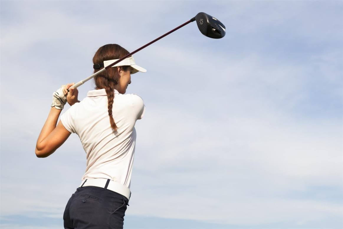 Women Swinging Golf Club