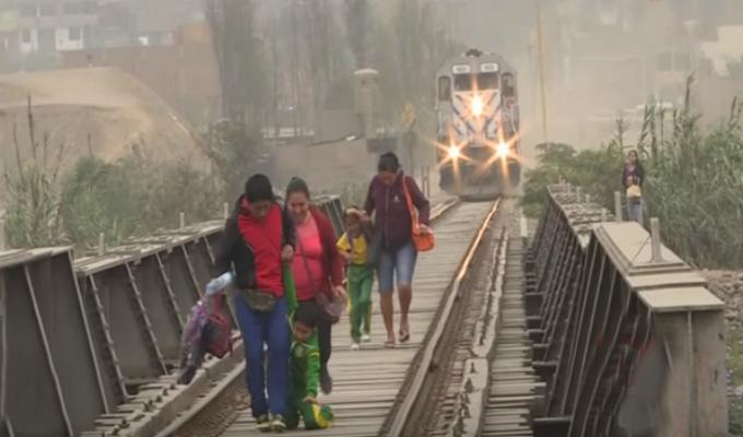 Padres con sus hijos arriesgan su vida para ganar el paso al tren