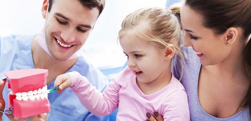 plano odontológico infantil : imagem de pais ensinando a criança a fazer escovação dos dentes