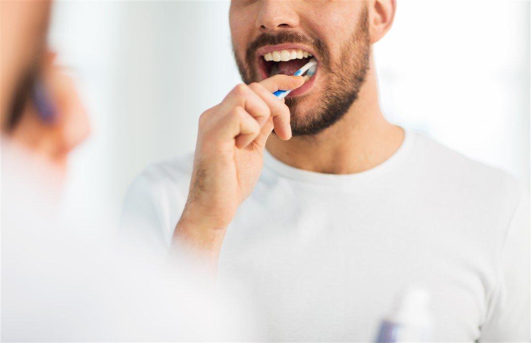 Homem fazendo a escovação dos dentes