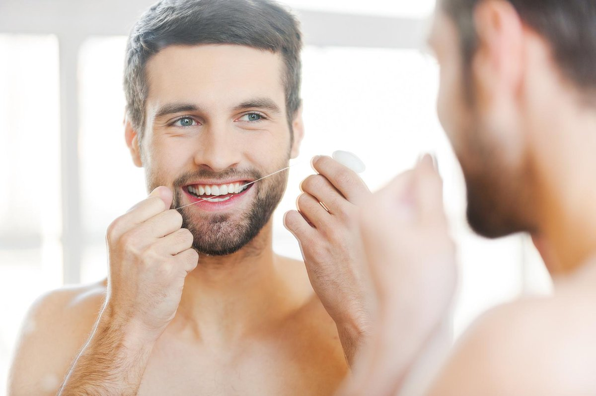 homem fazendo a limpeza dos dentes com fio dental