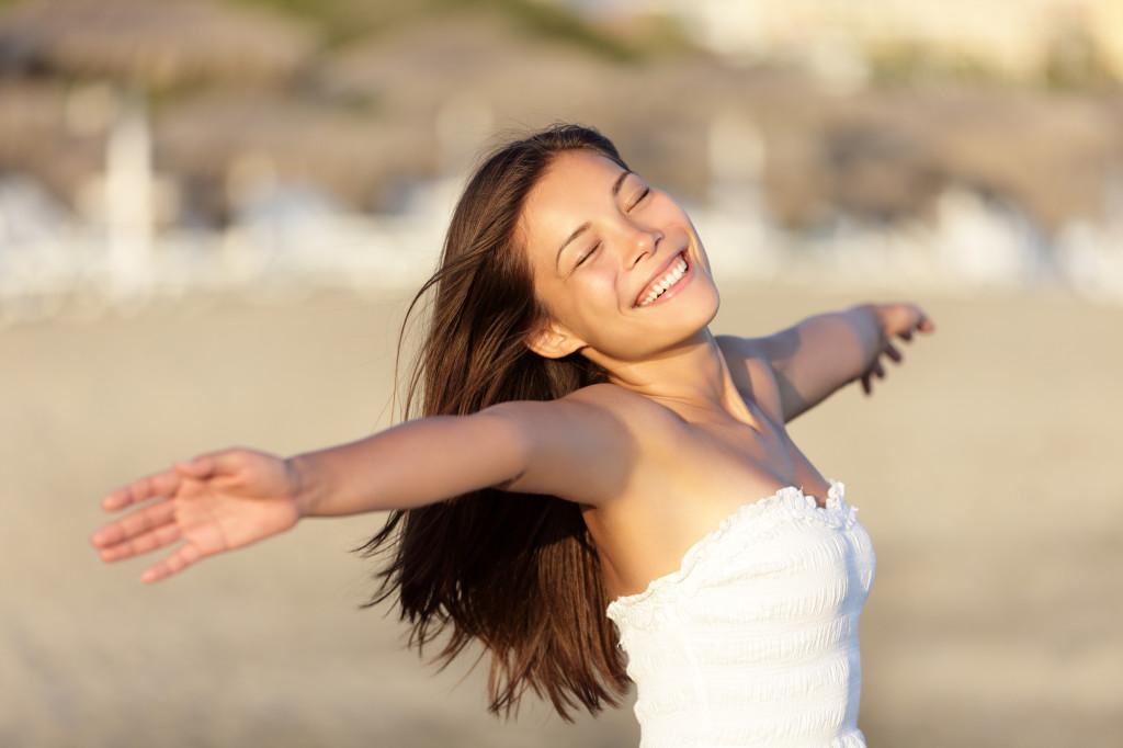 Imagem de mulher com braços aberto e sorrindo