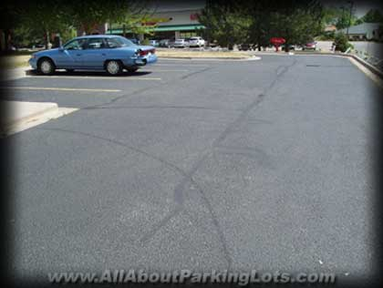 oil based asphalt sealer on an asphalt parking lot