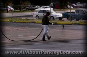 sealcoating an asphalt parking lot with a polymer sealer