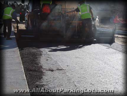 an asphalt paving contractor laying a new asphalt parking lot