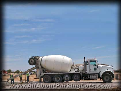 a concrete truck pouring concrete for a new concrete parking lot