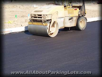 a new asphalt parking lot being installed and the roller compacting the asphalt while it's hot