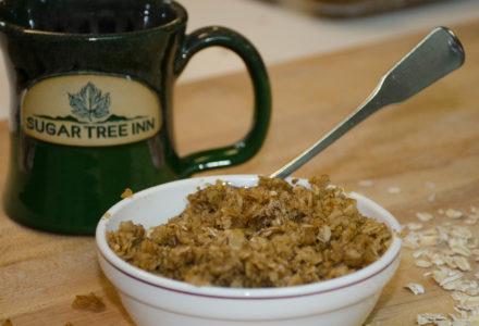 Bowl of baked oatmeal with Sugar Tree Inn coffee mug behind bolw