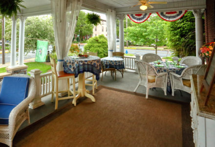 Covered side porch set with tables and decorated with red, white, and blue bunting.