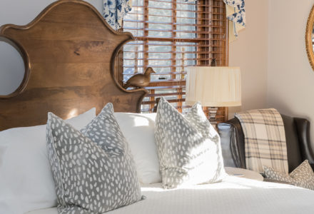Queen headboard with hand carved bird and luxurious grey pillows