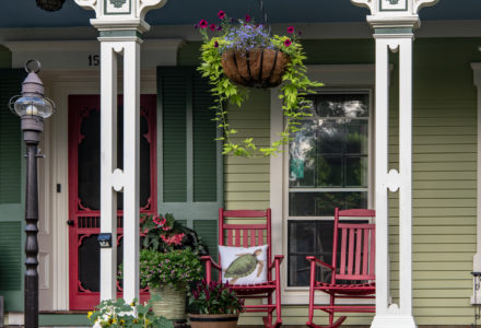Red rocking chairs with hanging baskets on the front porch