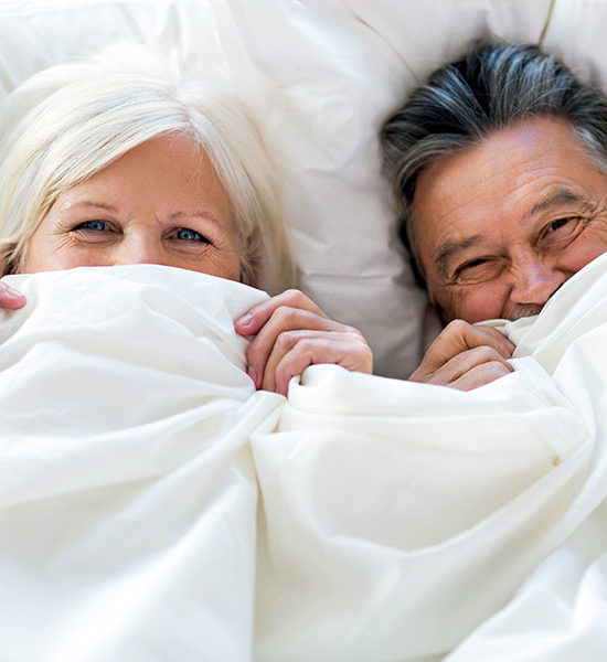 Sleep in, couple in bed laughing under the covers