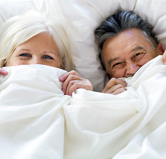 Couple in bed giggling with sheets pulled up, bnbfinder bed and breakfast directory