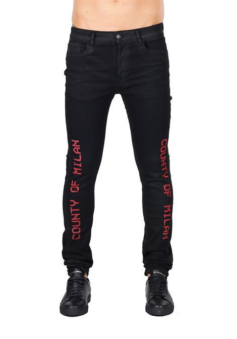 JEANS IN DENIM NERO CON LOGO STAMPATO MARCELO BURLON | Jeans | CMYA007F188701371020